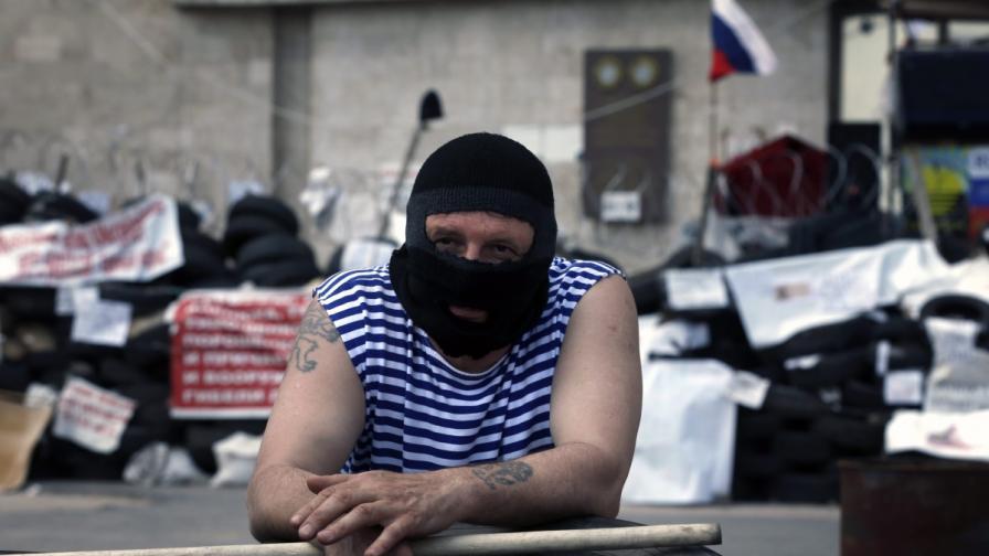 Поддръжник на новообявената Донецка народна република стои на пост пред сградата на областната администрация в Донецк