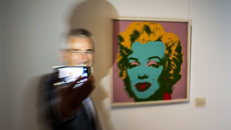 Почитател на Анди Уорхол се снима с известния портрет на Мерилин Монро