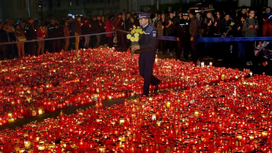 Полицай минава покрай килим от свещи пред клуба, в който загинаха 32 души в петък вечерта