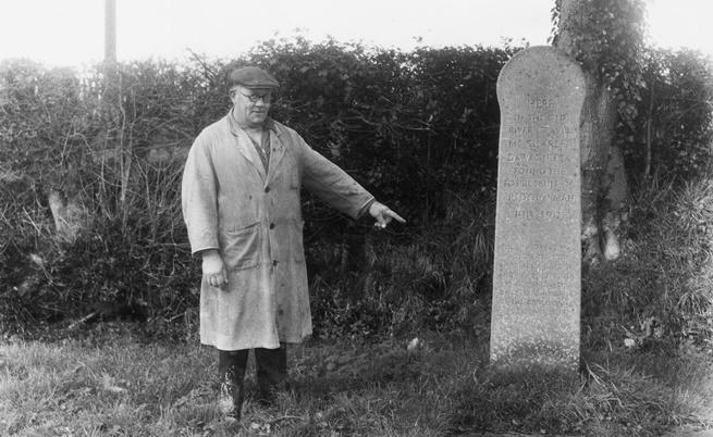 Джак Роджърс посочва надгробния камък на Пилтдаунския човек, открит през 1912 г. в Съсекс, Англия, и за който се предполагало, че е живял преди 500 000 години, преди да стане ясно, че откритието е лъжа.