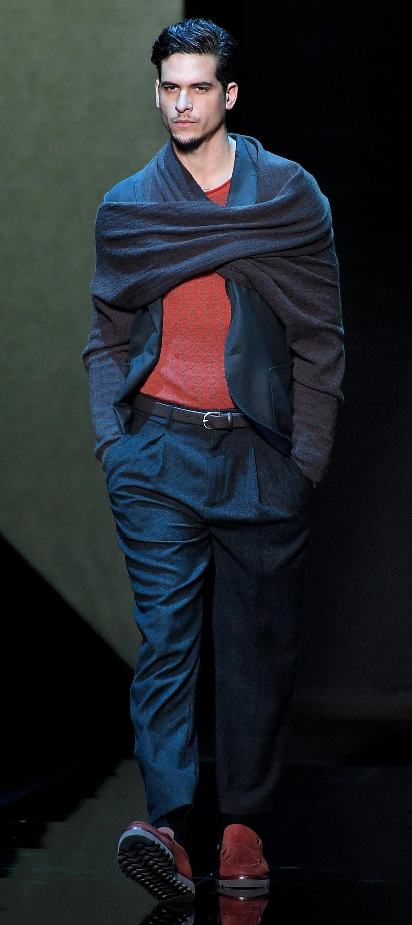 """Господстващи текстура и силует - с тези думи можем да опишем новата колекция за сезона есен/зима 2017-2018 г. на """"Армани"""", която бе представена в края на Седмицата на модата в Милано. Като свързваща нишка в цялата колекция на Джорджо Армани са дълги, увити около ръцете шалове, които се завързват отпред.За мъжете """"Армани"""" е предвидил панталони, които стигат до глезена, сака без хастар, както и жилетки от ангорска вълна с качулка, носени върху бели ризи."""