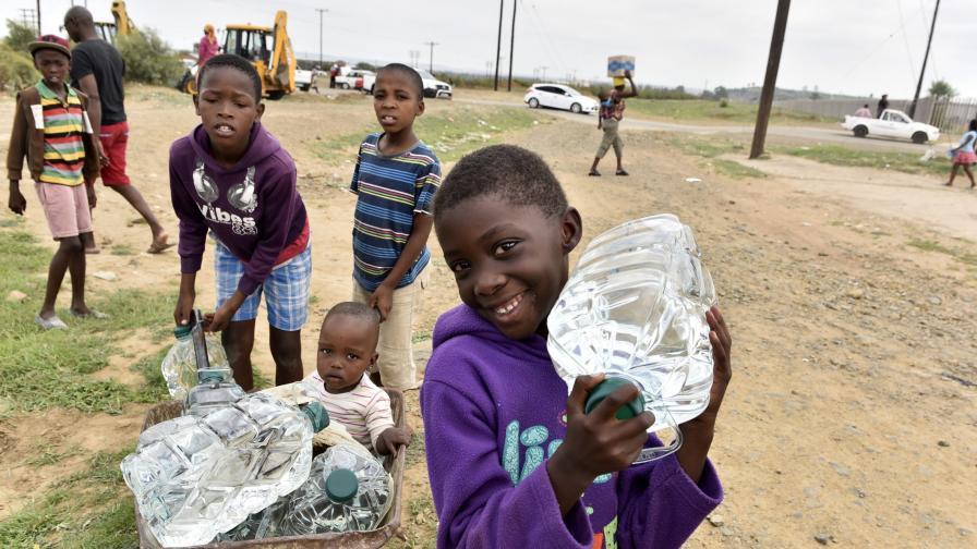 Деца в засегнат от суша район на Южна Африка се снабдяват с вода, доставена от доброволческа програма.