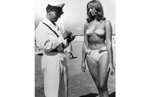 1957 г., полицай пише глоба на жена, която носи бикини на италиански плаж