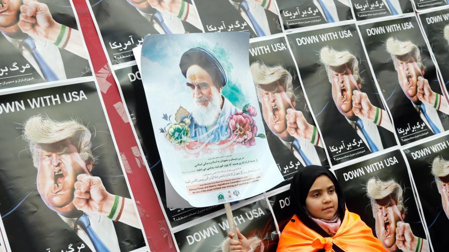 Момиченце държи постер на покойния основател на Ислямската република Аятолах Хомейни пред карикатури на Доналд Тръмп