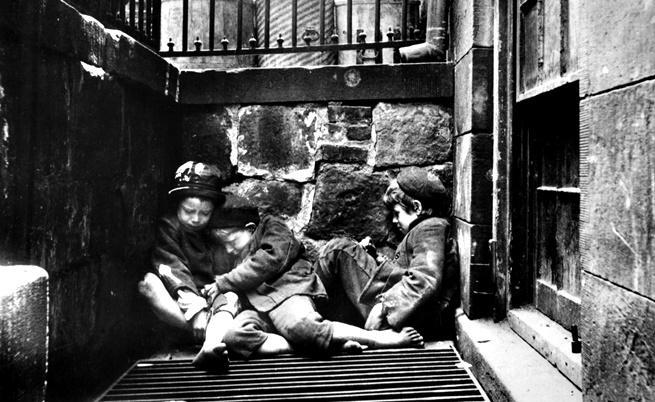 Три бездомни арабчета са се сгушили едно в друго, за да се стоплят.
