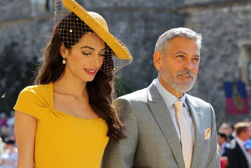 <p>Джордж Клуни, с чудесен официален костюм, и Амал - с невероятна жълта рокля и шапка.Обожаваме жълто и мислим, че Амал Клуни е взела чудесено решение при избора си на тоалет за кралската сватба.</p>