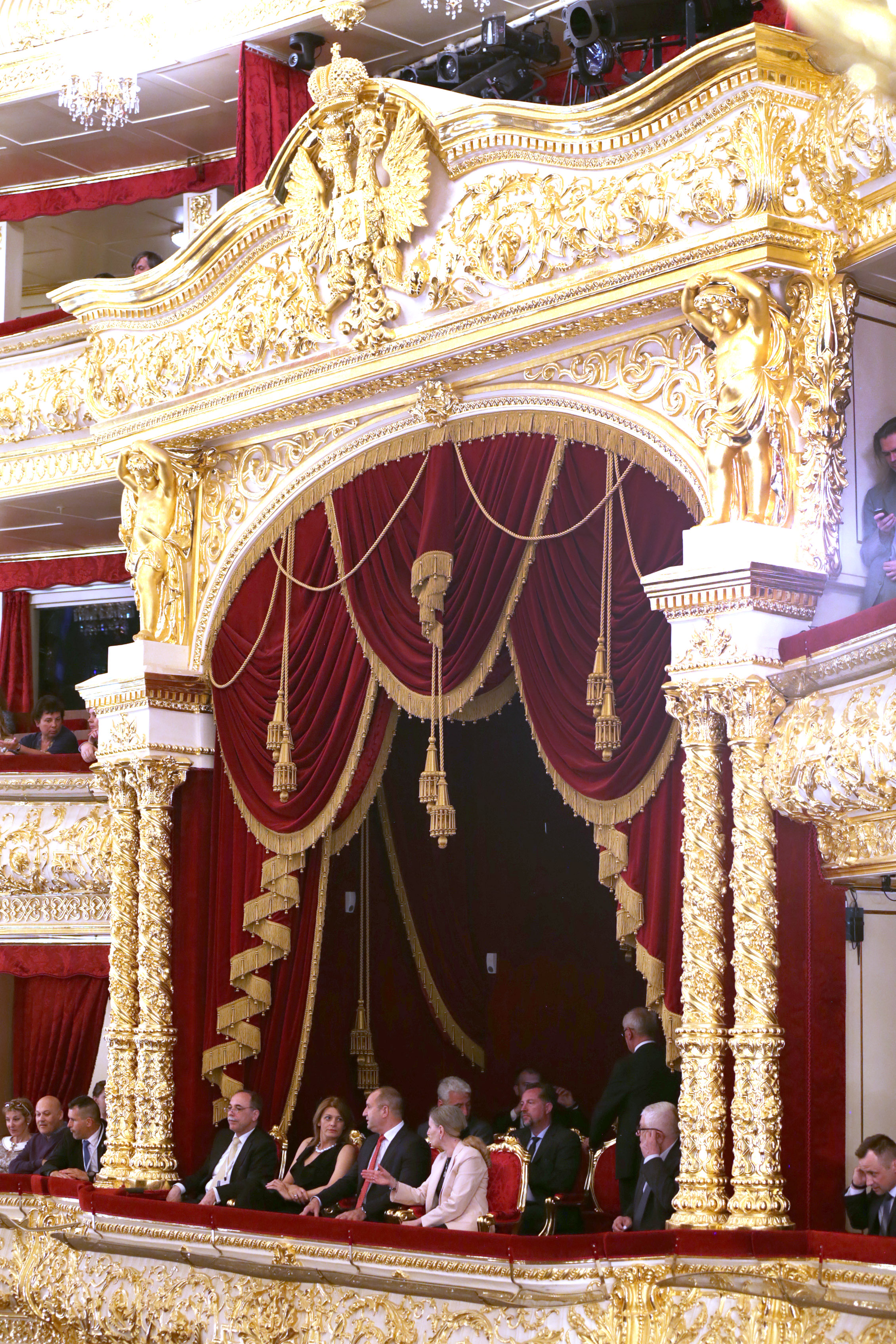 """В Болшой театър президентът Румен Радев и съпругата му Десислава присъстваха на оперната постановка """"Зигфрид"""" от Рихард Вагнер на Софийската опера и балет. Десислава Радева е заложила на черен гащеризон с отворено деколте. Тоалетът е съчетан със светли обувки на висок ток, както и колиев същия цвят."""