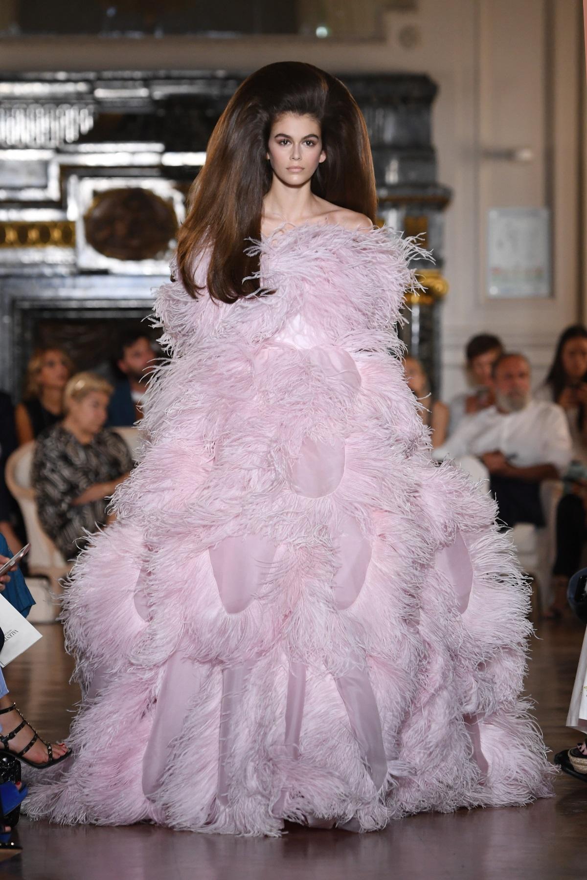 """Прическите на моделите от ревюто на """"Валентино"""" наподобяват стила на актрисатаПрисила Пресли в деня на сватбата ѝ с Елвис. Стилистът на шоуто Джош Ууд споделя, че са били нужни 150 часа за направата на косите на моделите, 50 перуки и екип от 11 човека."""