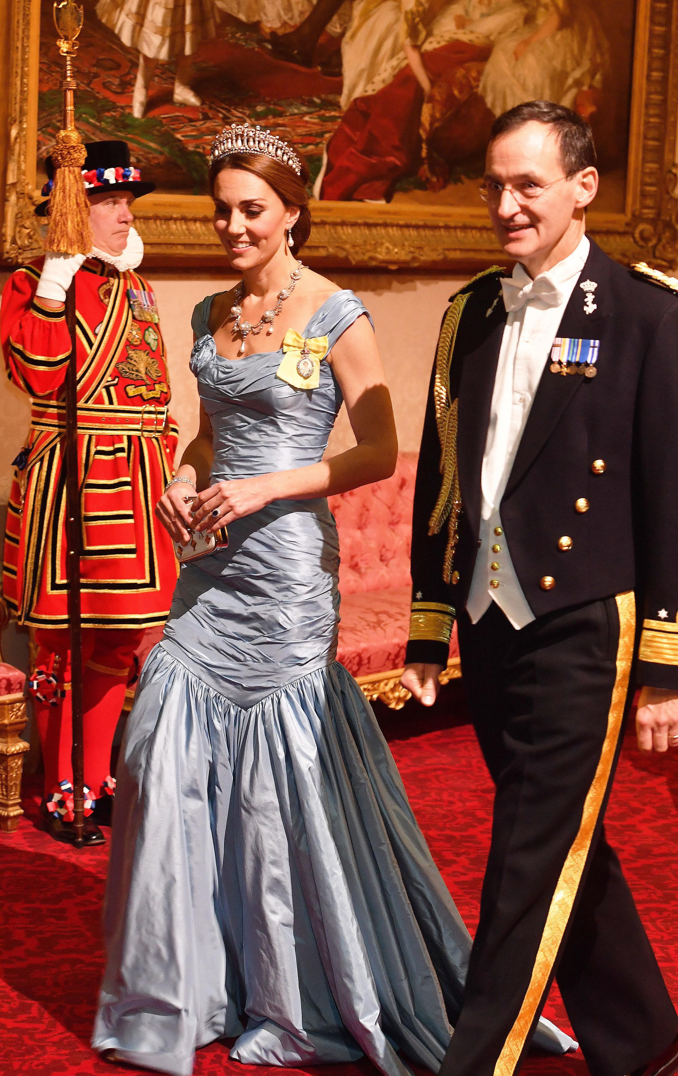 """За пореден път херцогинята на Кеймбридж заложи на рокля без ръкави, дело на Александър Маккуин. Елегантната рокля е в синята гама. Прическата на Кейт изцяло подхожда на тоалета, а бижутата й го правят още по-впечатляващ, пише сп. """"Харпърс базар"""". Херцогиня Мидълтън е заложила на красива тиара с перли, която по-рано е била любима на покойната принцеса Даяна. Освен тиарата, Кейт носи и красива огърлица със скъпоценни камъни и перли, допълнена от обеци."""