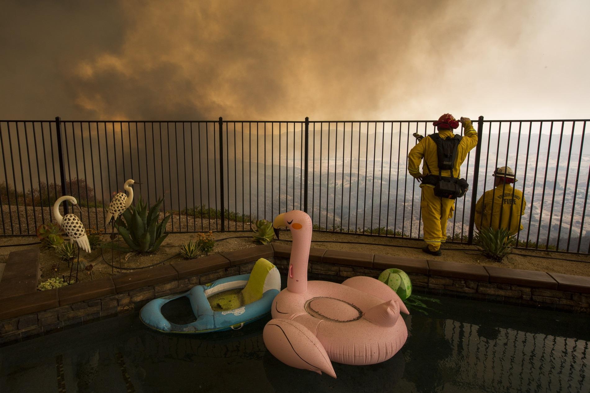 Пожарникарите наблюдават от двор огъня, заплашил стотици домове в Калифорния, САЩ, 9 август 2018 г. При нов пожар през ноември загинаха повече от 40 души, а хиляди сгради бяха унищожени, включително домовете на знаменитости като Джерард Бътлър, Майли Сайръс