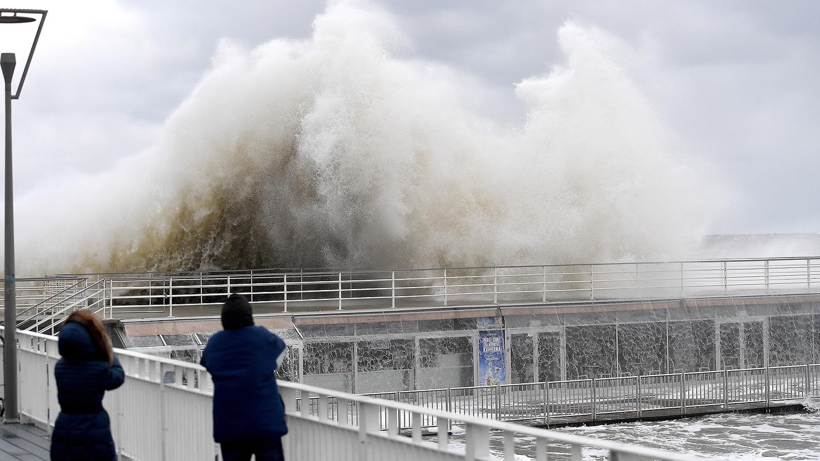Хора наблюдават бурните вълни на кея в Колобжег, Полша, на 2 януари 2019 г. Институтът по метеорология и управление на водите издаде предупреждение за силен вятър в крайбрежната зона.