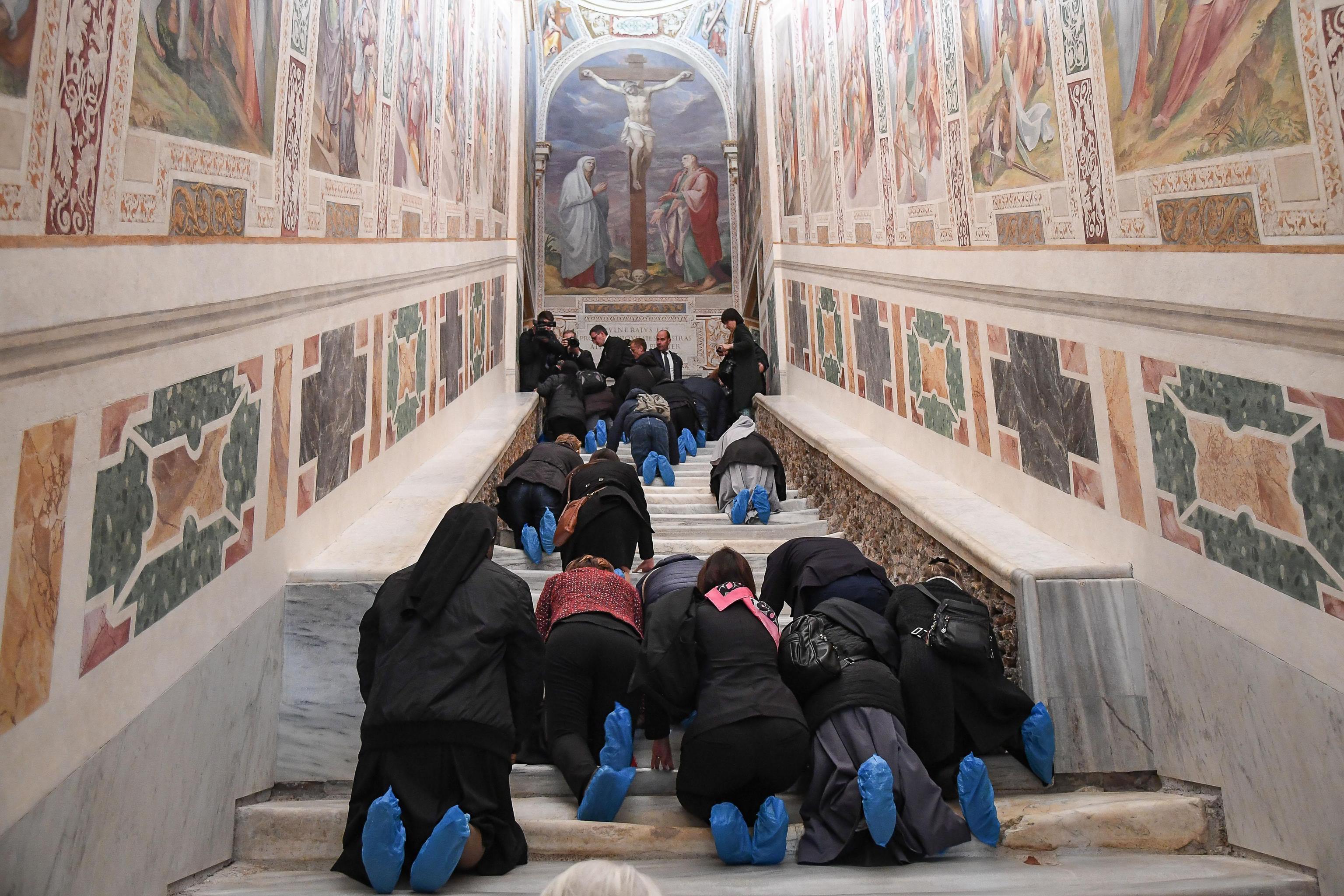 Множество вярващи побързаха да изкачат мраморната стълба, пълзейки на колене, както са го правили милиони поклонници преди тях през вековете.