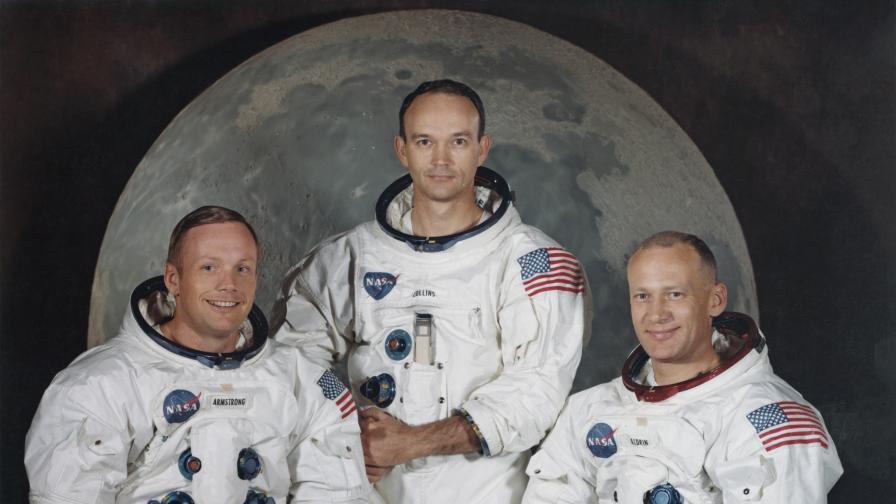 Екипа на Аполо 11. На снимката са Майкъл Колинс, Нийл Армстронг и Бъз Олдрин, позиращи пред голям модел на Луната.