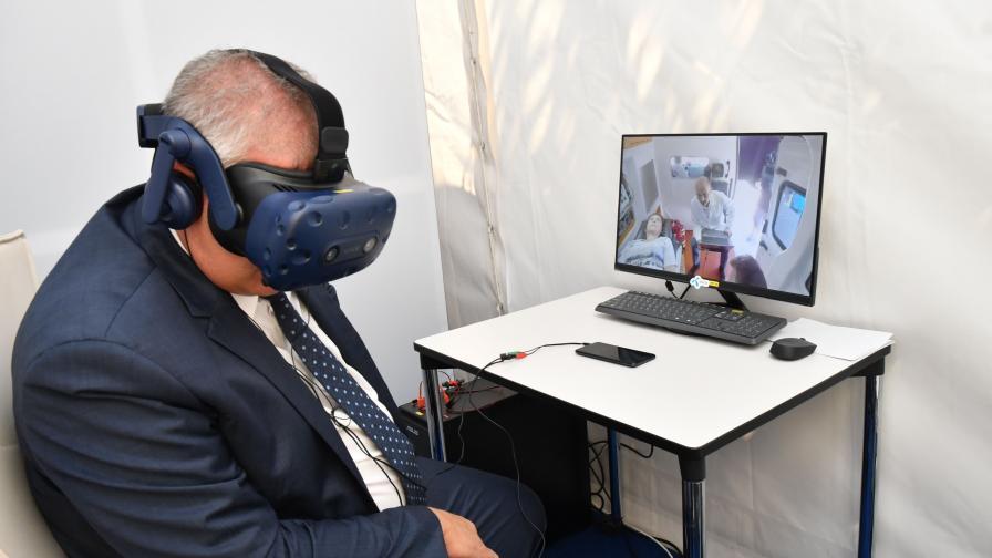 Професор Асен Балтов използва очила за виртуална реалност, за да извърши медицински преглед от разстояние.