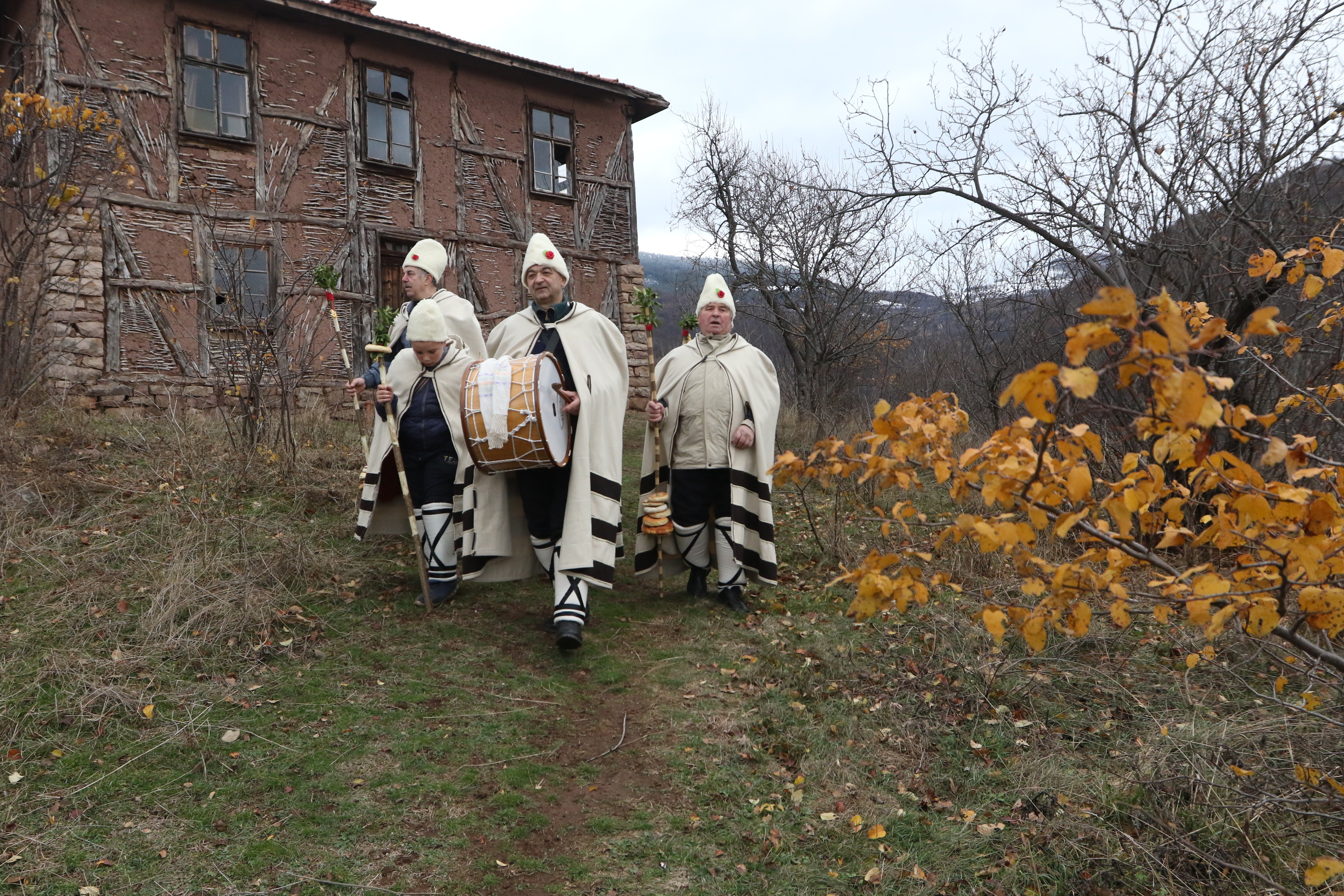 """Облечените празнично коледари са с накичени с китки калпаци, а в ръцете си носят """"шарени тояги""""."""