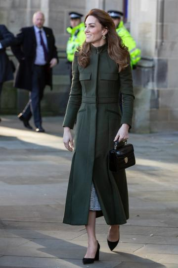 <p>Месец по-рано херцогинята на Кеймбридж се появява с тъмнозелено палто Alexander McQueen, правено по поръчка. То отново е в строг, консервативен стил, вдъхновен от формите и цветовете на военните шинели. Визията е допълнена от аксесоари в черно - обувки на ток Gianvito Rossi ($695) и кожена чантичка Aspinal of London ($725).</p>
