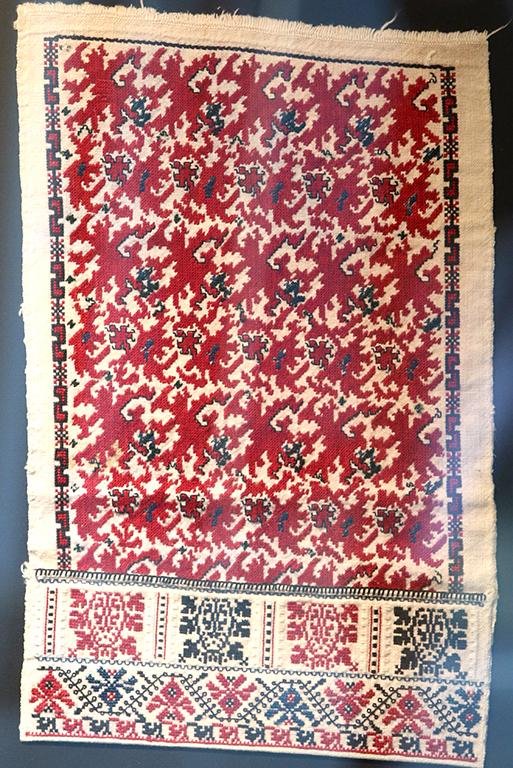 <p>Свиленица от около 1901 година. Виждат се листа, стъбла и клонки, разлюлени от вятъра. Този древен символ на лозата символизира младост, плодородие, вечност, изобилие и дом. Подладжицата е съставена от гербове от лозници, оградени с бяло. Те са необичайно широки с черен отплит, омекотен с бели и сини вълни.</p>