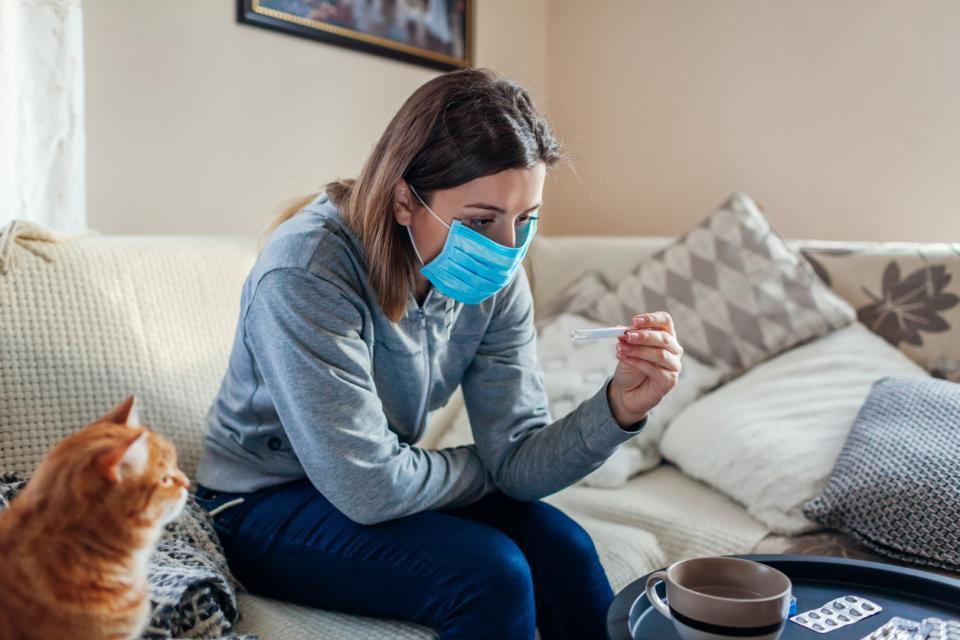 жена с маска срещу коронавирус у дома
