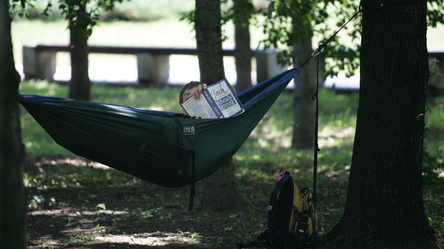 Младеж чете книга в хамак, опънат между две дървета край НДК