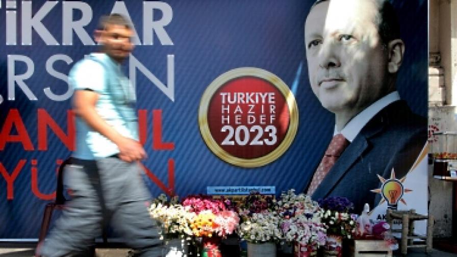 Мъж минава покрай предизборен плакат на ПСР