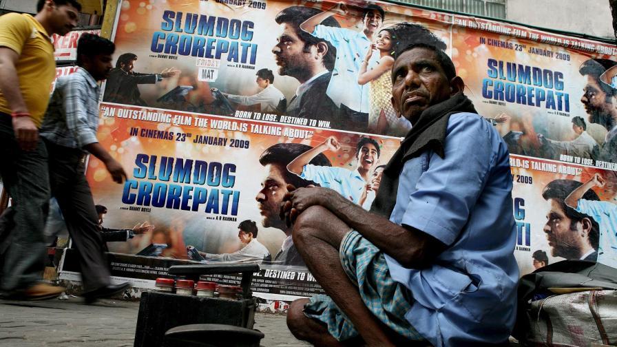 Беден обущар клекнал на улицата под плакатите за филма