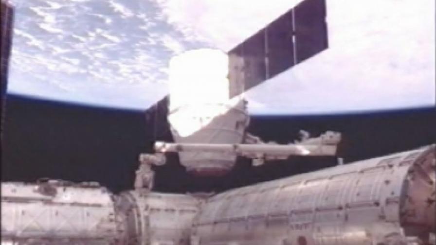 """Частният космически кораб """"Дракон"""" по времена разкачването от МКС, извършено с  помощта на 17-метрова ръка-манипулатор"""