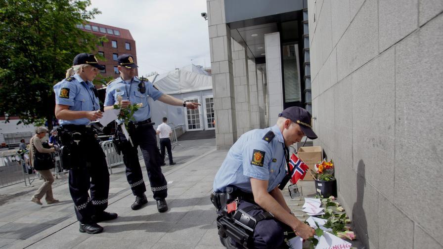 Норвежки полицаи внимателно разчистват цветя, оставени в памет на жертвите на Брайвик