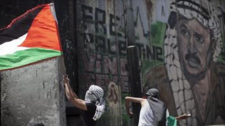 Маскирани палестинци хвърлят камъни по израелски гранични полицаи (не се виждат на снимката) при стената, изрисувана с портрет на Ясер Арафат, която разделя Палестина от Израел на западния бряг (фотография от  май 2012 г.)