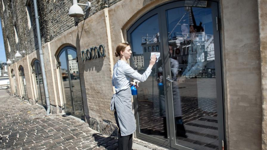 Служителка на ресторанта почиства витрината на входа