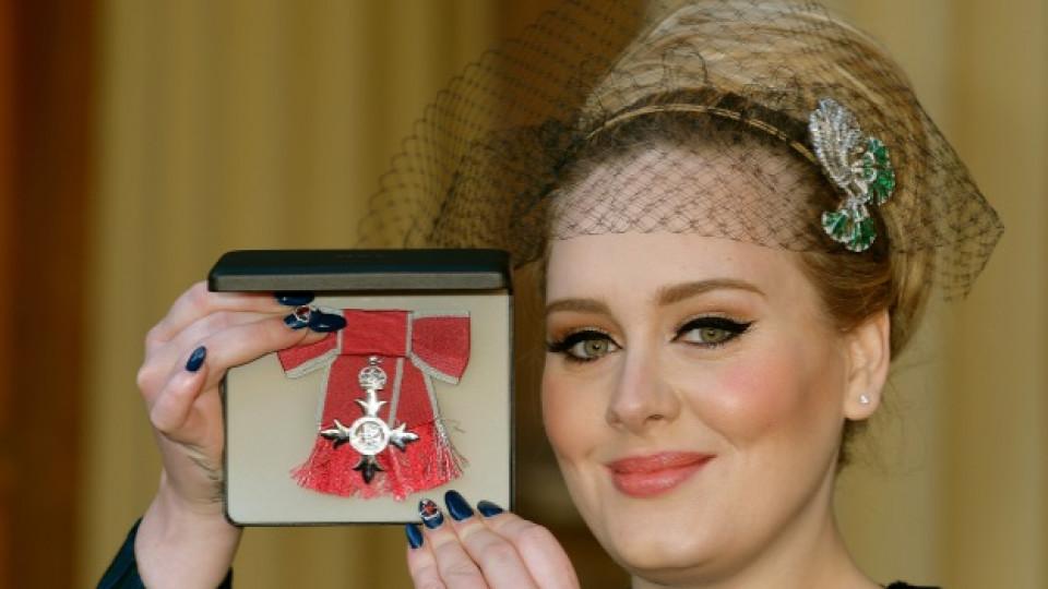 Адел позира с Ордена на Британската империя, връчен ѝ лично от принц Чарлз